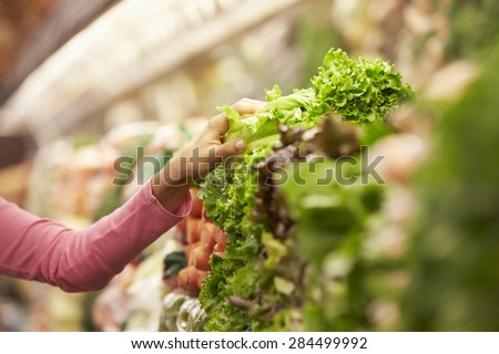 Close Up Of Woman Choosing Salad In Supermarket - stock photo