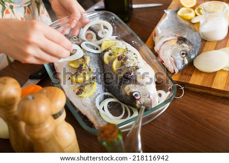 Close-up of woman cooking fish  in frying pan at home kitchen  - stock photo