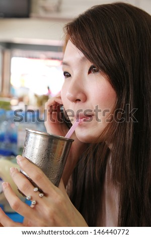 Close up of woman drinking and talking on mobile phone.