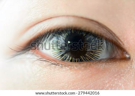 Close up of woman eye wearing fancy contact lens - stock photo