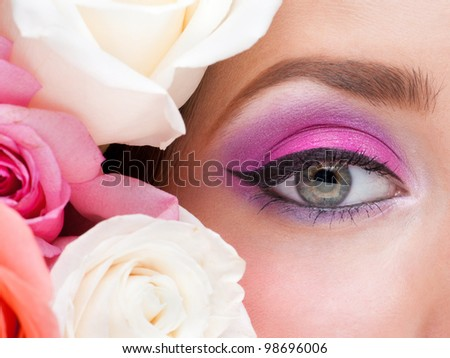 Close-up of woman eye with bright stylish makeup and pink roses