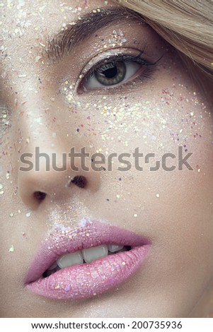 Close up of woman face with glitter on face - stock photo