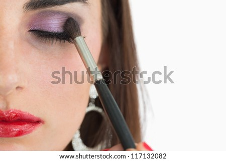 Close up of woman getting applied red lips and smoky eyes - stock photo
