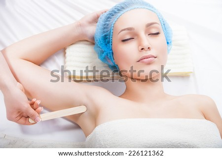 Close up of woman getting waxing armpit by beautician in a beauty salon