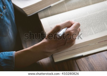 Close up of woman hand pointing a pen reading text book in library. Education concept.