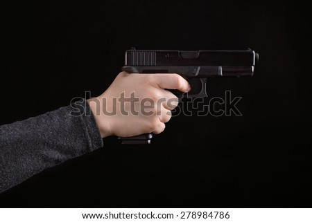 Close up of woman hand with aiming gun on a black background - stock photo