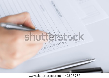 close up of woman hand with blank questionnaire or form