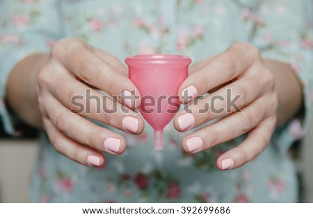 Close up of woman hands holding menstrual cup - stock photo