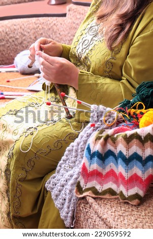Close-up of woman hands knitting with stylish knitting needles - stock photo