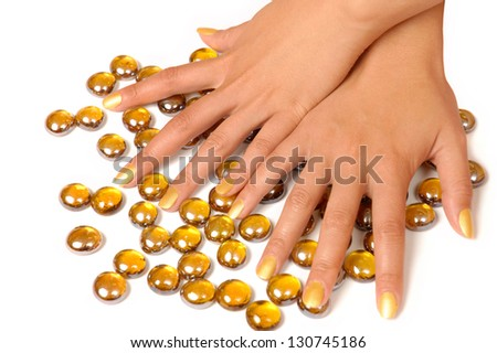 Close up of woman hands manicure with gold nail polish and yellow stones isolated on white background
