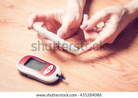 Close-up Of Woman Hands Testing High Blood Sugar With Glucometer, Blood glucose meter, The blood sugar value is measured on a finger, Syringe pen with insulin and glucometer - stock photo