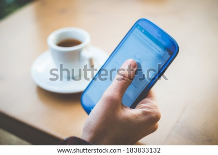close up of woman hands with smart phone and cup of coffee at the bar - stock photo