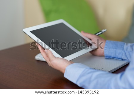 Close-up of woman holding a tablet with blank screen and taking notes on a paper notebook with a pen - stock photo