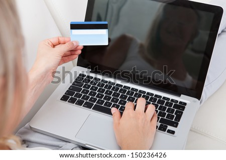 Close-up of woman holding credit card and using laptop