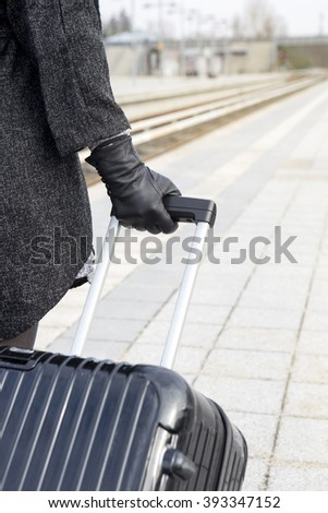 close-up of woman holding her suitcase at train station