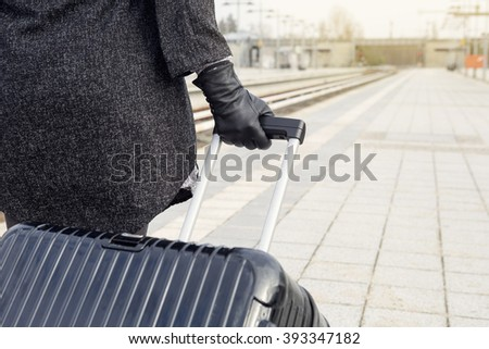 close-up of woman holding her suitcase at train station - stock photo