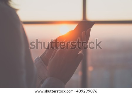 Close-up of woman holding smartphone in her hands, typing, texting, using touchscreen at wi-fi zone. - stock photo