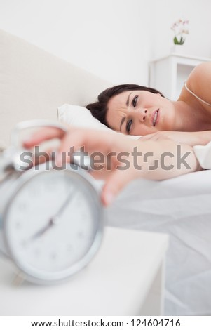 Close-up of woman in bed extending hand to alarm clock - stock photo