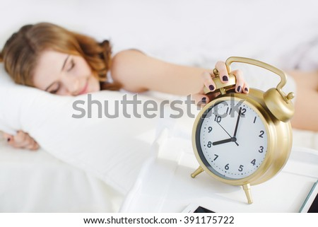 Close-up of woman in bed extending hand to alarm clock. girl turns off the alarm clock waking up in the morning from a call. Young sleeping woman and alarm clock in bedroom at home