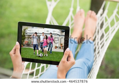 Close-up Of Woman In Hammock Watching Movie On Digital Tablet