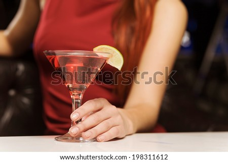 Close up of woman in red dress with cocktail in hands - stock photo