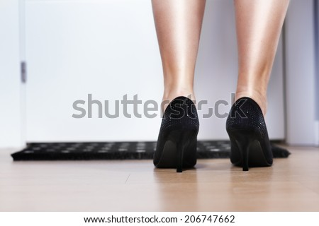 Close up of woman leg in black shoes. Back view. Front door - stock photo
