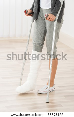 Close-up Of Woman Leg In Plaster Cast Using Crutches While Walking - stock photo