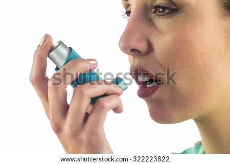 Close-up of woman looking away while using asthma inhaler against white background - stock photo