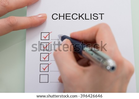 Close-up Of Woman Marking On Checklist Form With Red Pen - stock photo