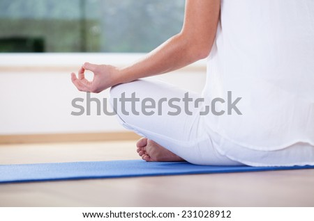 Close-up of woman meditating in lotus position - stock photo