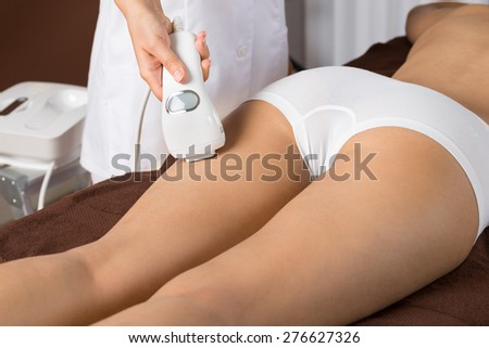 Close-up Of Woman Receiving Epilation Laser Treatment On Thigh - stock photo