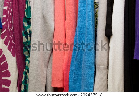 Close up of woman's clothing hanging in closet, showing various materials and colors