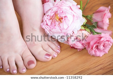 close-up of woman?s feet with pink nail polish and fresh pink flowers on wooden floor
