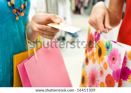 Close-up of womanâ??s hand holding credit card and bags with another female near by during shopping in the mall - stock photo