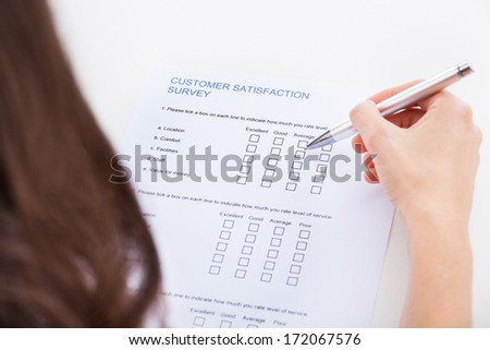 Close-up Of Woman's Hand Holding Pen Over Survey Form - stock photo
