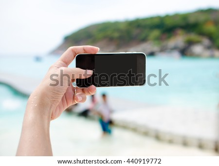 Close up of woman's hand holding smartphone, mobile, smart phone over blurred beautiful blue sea - stock photo