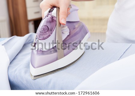 Close-up Of Woman's Hand Ironing Clothes On Ironing Board - stock photo