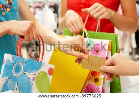Close-up of woman?s hand passing over credit card to shop assistant on background of another female - stock photo