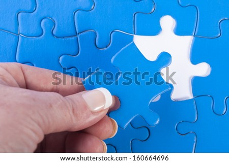 Close up of woman's hand placing missing piece in Jigsaw puzzle  signifying problem solving and decision making - stock photo
