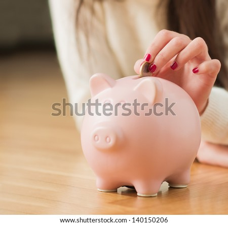 Close-up Of  Woman's Hand Putting Coin In Piggy bank, Indoors