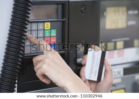 Close-up of woman's hand using ATM machine at fuel station - stock photo