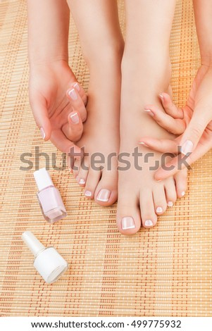 Close-up of woman's hands and feet after pedicure and manicure on a bamboo mat