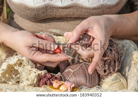 Close-up of  woman's hands crocheting outdoors - stock photo