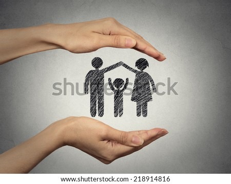 close up of woman's hands protecting happy family, mother, father, child. Family abstract in palms on grey wall background. Safe childhood, parenting. Love care compassion safety secure future concept - stock photo