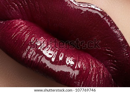 Close-up of woman's lips with bright fashion dark red glossy makeup. Macro lipgloss cherry make-up. Sexy kiss - stock photo