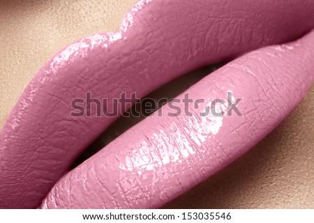 Close-up of woman's lips with bright fashion pink glossy makeup. Macro magenta lipgloss make-up  - stock photo