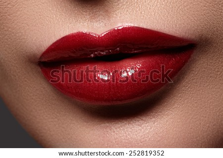Close-up of woman's lips with bright fashion red glossy makeup. Macro cherry color lipgloss make-up. Sexy kiss - stock photo