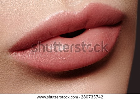 Close-up of woman's lips with fashion natural beige lipstick makeup. Horizontal macro sexy pale lipgloss make-up  - stock photo