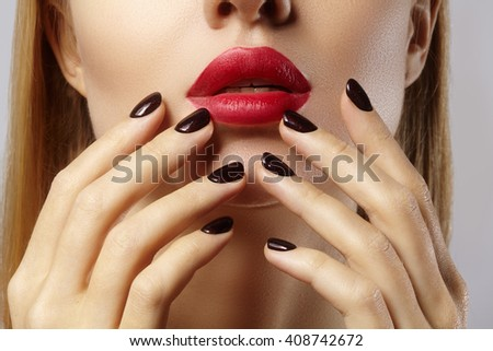 Close-up of woman's lips with fashion red make-up and manicure. Beautiful female full lips with perfect makeup. Classic visage. Part of female face. Macro shot of beautiful make up on full lips.  - stock photo