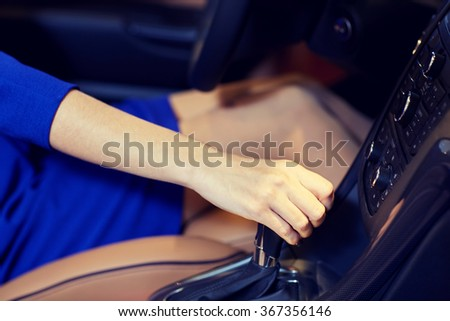 close up of woman shifting gears on gearbox in car - stock photo